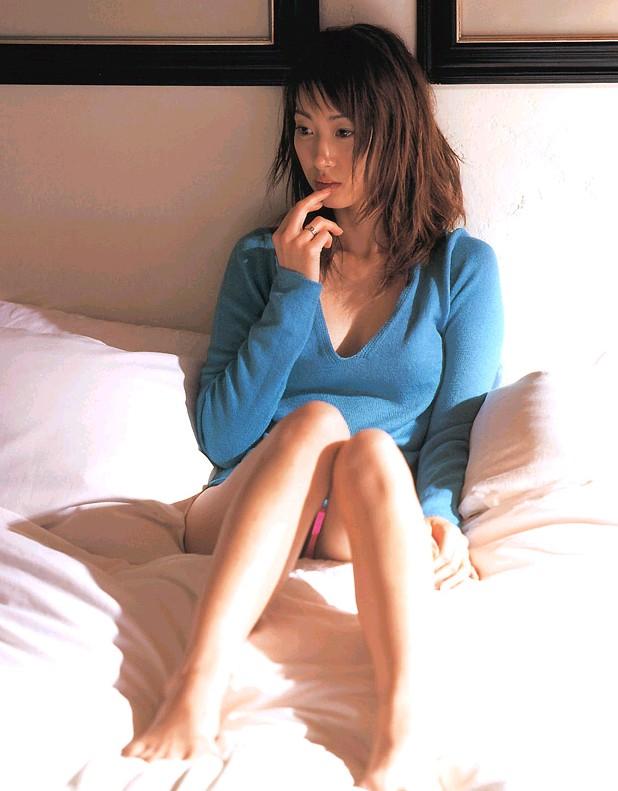 ピンクの水着に水色のセーターを着てベッドの上に座る坂下千里子